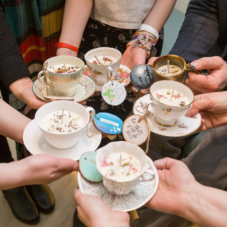 Friends standing in a circle hold out various teacups into which they have poured wax to create candles.  20 Different Ways To Recycle, Upcycle and Repurpose Old China