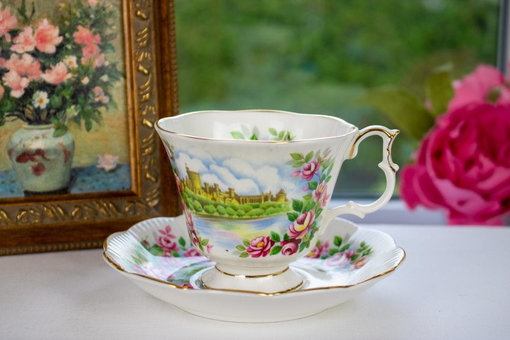 A Royal Albert teacup and saucer sits on a table with a white table cloth in front of a window. In the background, there are pink peonies to the right and a painting in a small vintage frame to the left.