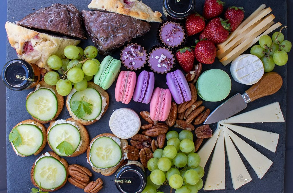 A slate board holds a variety of finger foods including grapes and strawberries, cheeses, macarons and scones. A new take on Afternoon Tea